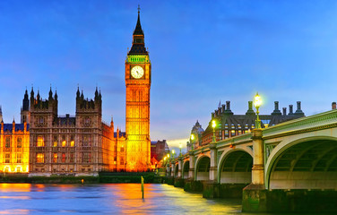 View of the Houses of Parliament and Westminster Bridge along River Thames in London at night.