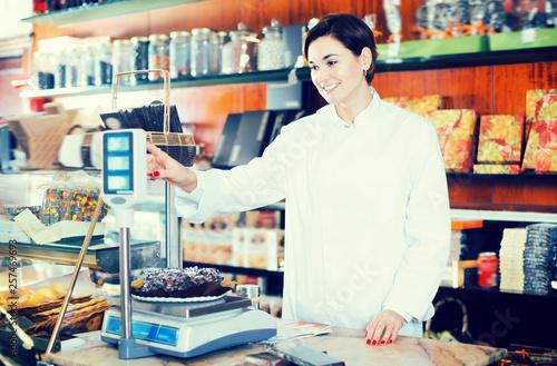 Leinwandbild Motiv Young seller weighing festive chocolate cake