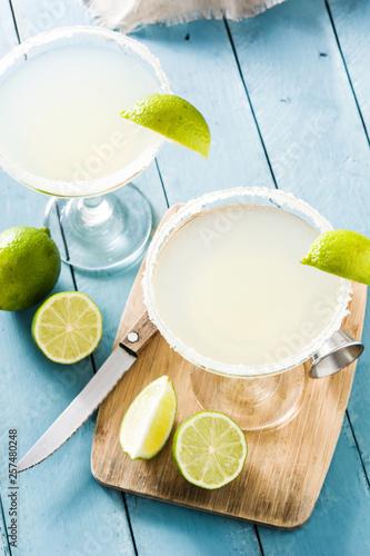 Leinwandbild Motiv Margarita cocktails with lime in glass on blue wooden table