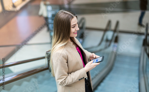Young woman on escalator © pikselstock
