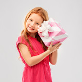 birthday and people concept - lovely red haired girl with gift box over grey background