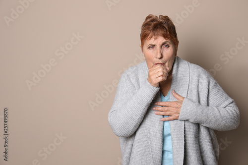 Leinwandbild Motiv Elderly woman coughing against color background. Space for text