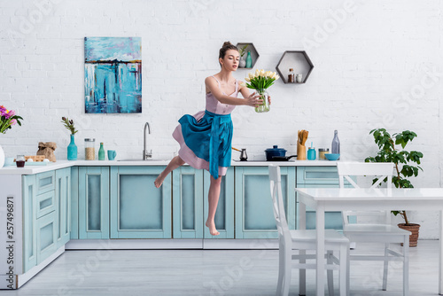 Leinwanddruck Bild beautiful barefoot girl in elegant dress and apron flying in air with bouquet of tulips in glass jar in kitchen