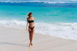 Tanned girl in black swimsuit and sunglasses walks along shore of beach