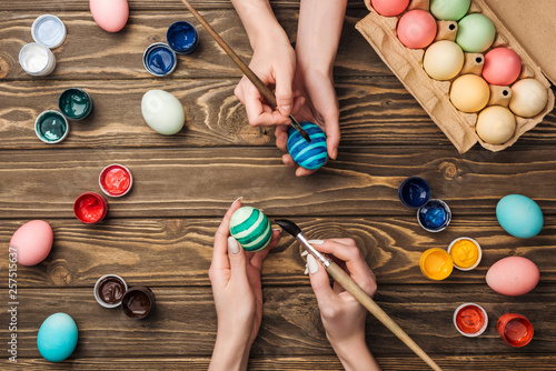 top view of women painting easter eggs at wooden table - 257515637