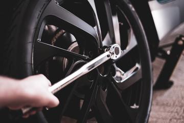 Mechaniker befestigt den Reifen mit einem Drehmomentschlüssel