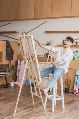 excited artist sitting on high chair at easel with canvas