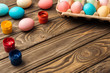 pastel easter eggs in cardboard box with acrylic paints on wooden table with copy space