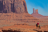 A Native American on horseback in a scenic view in Monument Valley.