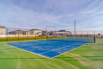 Tennis court against homes mountain and sky