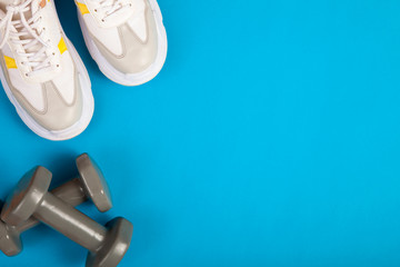 Fitness equipment. Sneakers, on blue background © busra