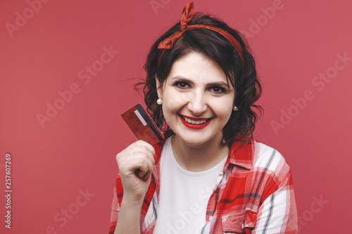 Picture of a smiling pretty girl holding red credit card in her hand © burdun