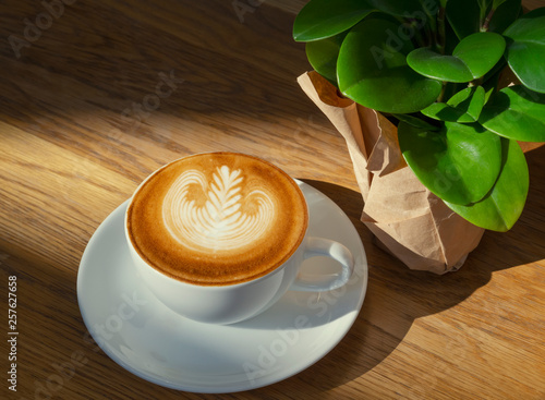latte or Cappuccino art coffee cup top view on wood table with sunlight in cafe.