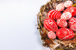 Closeup Easter red eggs with folk white pattern inside bird nest on white background. Top view.