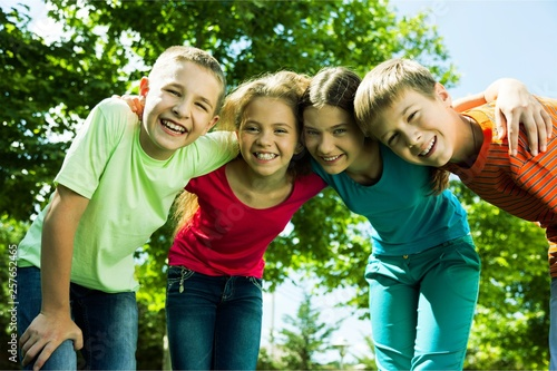 Happy smiling  diverse kids hugging in park © BillionPhotos.com