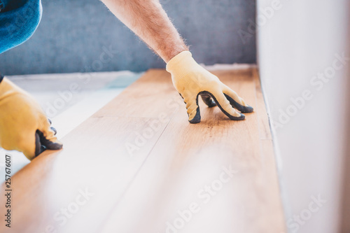 A man worker lays laminate - professional construction and finishing services © andrey gonchar