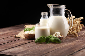milk products. tasty healthy dairy products on a table. sour cream in a white bowl, cottage cheese bowl, cream in a a bank and milk jar, glass bottle and in a glass