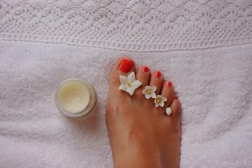 Cura dei piedi nella spa su asciugamano bianco con smalto rosso e fiori di gelsomino