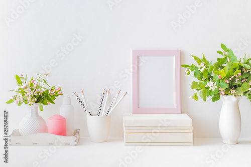 Home interior with decor elements. Pink frame, branches with green leaves in a vase, interior decoration - 257694017