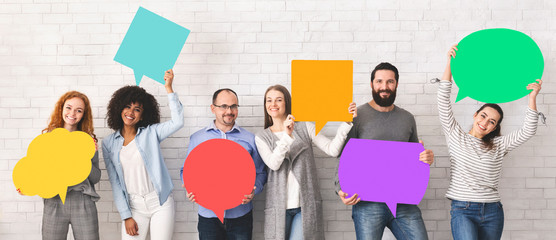 Group of diverse people holding colorful speech bubbles © Prostock-studio