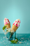 Melting ice cream cone with fruit syrup decorated white cherry blossom on blue background