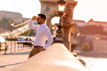 A businessman on a bridge covering his face