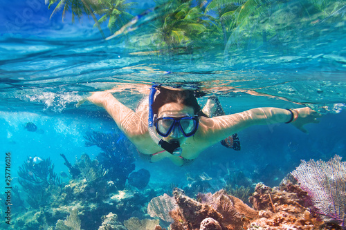 Leinwanddruck Bild Young woman at snorkeling in the tropical water