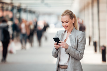 Beautiful smiling businesswoman using smartphone on the city street. © bnenin
