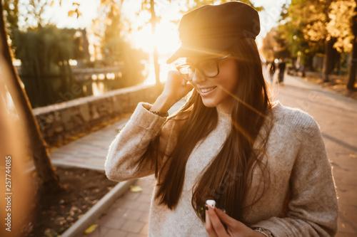 fototapeta na ścianę Beautiful young girl listening to music in the park through a wireless earpiece