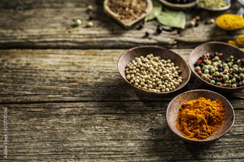 Spices in spoons on wooden background © nerudol