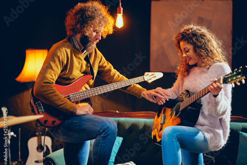 Caucasian woman playing acoustic guitar while man playing bass. Home studio interior. - 257749425