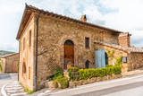 Val D'Orcia countryside in Tuscany with empty street in small town village with nobody and plants on typical stone house in Querce al Pino, Italy