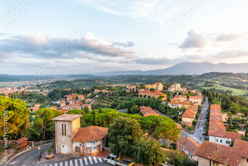 Chiusi sunset evening in Umbria, Italy with rooftop houses on mountain countryside rolling hills and street road with colorful picturesque cityscape with clouds