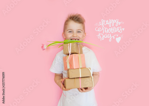 Leinwanddruck Bild A little boy holds gifts and a postcard for mom. Mother's Day to celebrate. Pink background.