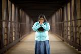 Hispanic Woman Praying While Holding Bible On A Bridge