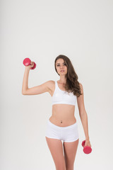 Portrait of young beautiful woman making physical exercises with dumbbells © Johnstocker