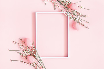 Easter composition. Easter eggs, photo frame, white flowers on pastel pink background. Flat lay, top view, copy space © Flaffy
