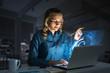 Leinwandbild Motiv Beautiful blonde in dark office working on laptop and getting net access