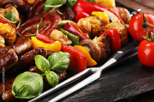 Assorted delicious grilled meat and skewer with vegetable on rustic table - 257845295