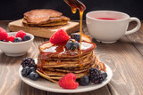 Pouring honey on Pancakes with blueberries and strawberries and cup of red juice