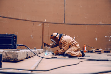 Worker in protective suit and mask crouching and welding in metal tower at construction site.