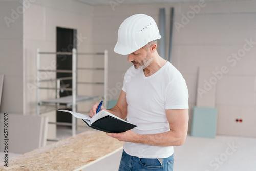 Builder making construction notes on a new build © contrastwerkstatt