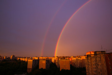 Rainbow over the city. Beautiful landscape. Busy town and nature concept. Purple sky.