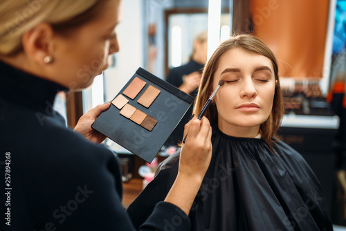 canvas print picture Visagiste and lady chooses cosmetic in makeup shop