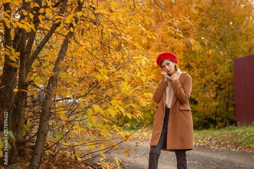 fototapeta na ścianę a girl in a brown coat and a red beret standing against the trees in autumn