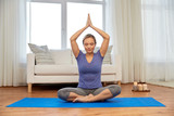 mindfulness, spirituality and healthy lifestyle concept - woman meditating in lotus pose at home