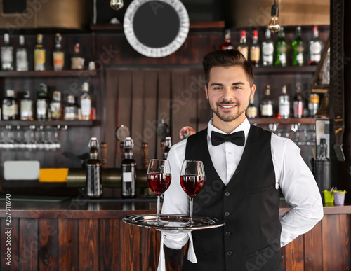 Young male waiter with glasses of wine in restaurant - 257911690
