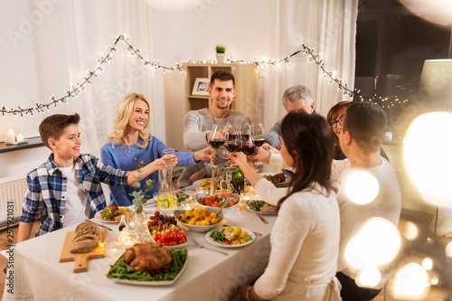 celebration, holidays and people concept - happy family having dinner party, drinking red wine and toasting at home - 257921031