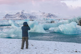 A photographer in a blue coat shooting glaciers on a cold winters day.