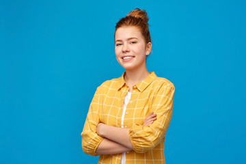 people concept - smiling red haired teenage girl in checkered shirt with crossed arms over bright blue background